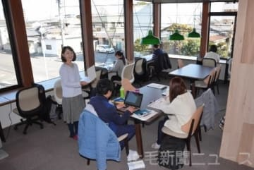ラウンジスペースで研修するカフェスタッフと清水社長(左)