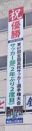 サッカー部の全国高校選手権優勝を祝い、青森山田高校校舎に掲げられた垂れ幕=21日午前