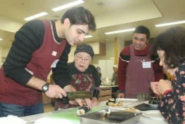 巻きずしの作り方を習う留学生(左端、右から2人目)ら=日出町保健福祉センター