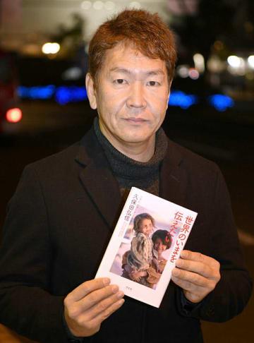 帰省先の大垣駅前で著書「世界のいまを伝えたい」を手にする久保田弘信さん=8日、大垣市高屋町