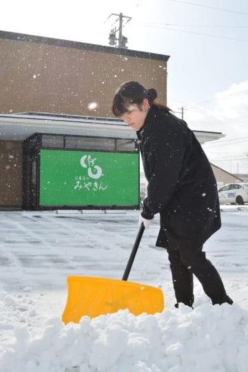 雪片付けに精を出す従業員=21日午前10時半ごろ、八戸市田向2丁目