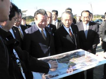 サーフィン会場整備計画の説明を聞く桜田五輪相(中央)=21日午前、一宮町の釣ケ崎海岸