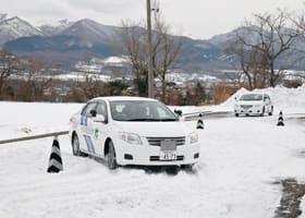 積雪のコースで慎重に運転する参加者