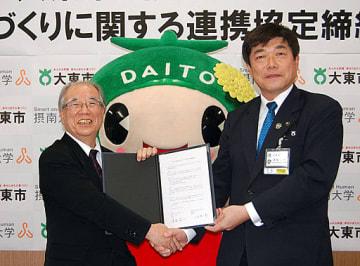 協定書を交わして握手する東坂市長(右)と八木学長=21日、大東市役所