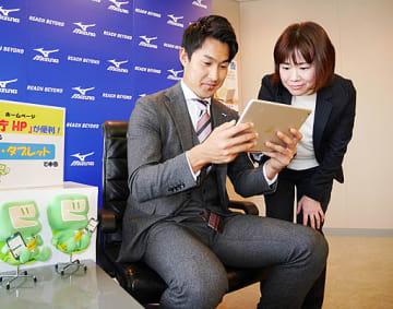 税務署員(右)の解説を受けながらタブレットに氏名などを入力する飯塚選手