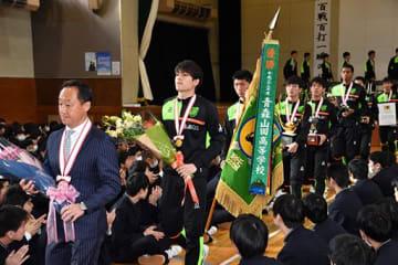 優勝旗とメダルを胸に全校生徒の祝福を受ける青森山田イレブン=22日午前、青森山田高校