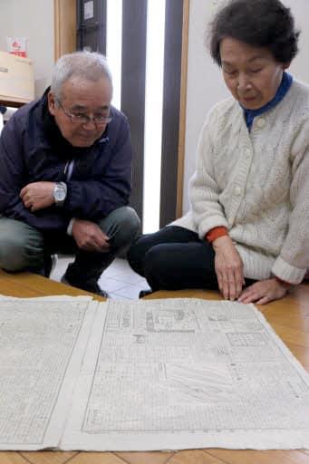 自宅で見つけた1910年12月の中国新聞朝刊を眺める小田さん夫婦