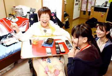 脳性まひで介助を受けながら1人暮らしをしている吉田詩織さん(左)=2018年12月、福井県福井市
