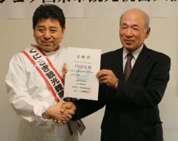 委嘱状を受け取る下村浩司さん(左)=22日、国東市国東町小原のビストロエスポワール