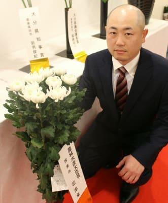 最高賞の輪ギクと、出品者「花未来」の小俣俊秀代表=22日、大分市のトキハ会館