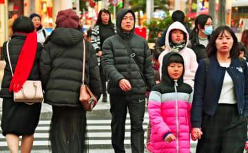 ダウンジャケットなどを着込み歩く人の姿もあった=22日午後5時38分、那覇市・国際通り(落合綾子撮影)