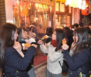 チーズハットグを味わう若者たち=水戸市三の丸、高松美鈴撮影