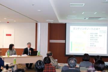 【事例を交えながらACPについて話す西川さん(後方・左から2人目)=桑名市内堀のもりえい病院で】