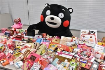 ファンからもらったバレンタインチョコを前に喜ぶくまモン=2018年2月15日、県庁