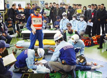 多くの見学者が見守る中、模擬傷病者に処置を施す救急隊員=22日、東大阪市の高度専門教育訓練センター