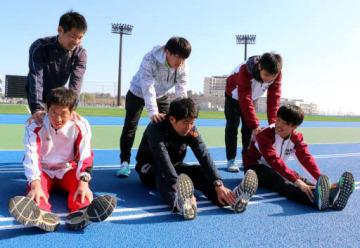 練習後に柔軟体操をする藤田監督(左後ろ)たち岩国市の選手