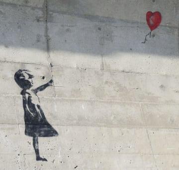 漁港の防波護岸に描かれたバンクシーの作品「少女と風船」に似た絵=22日、千葉県九十九里町(同町提供)