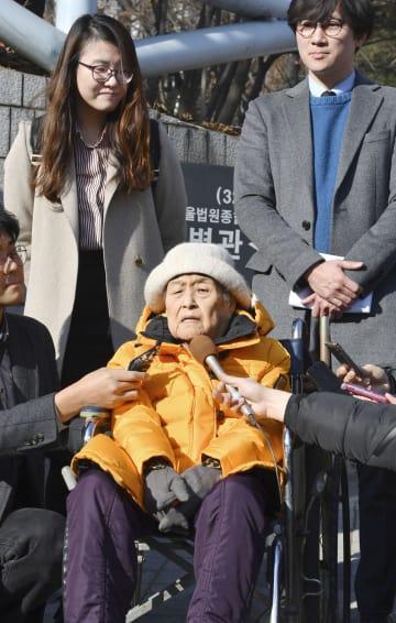 判決後、記者会見する原告の李春綿さん(中央)ら=23日、ソウル(共同)