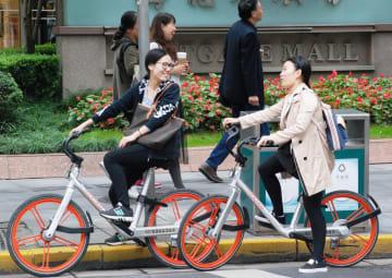 上海でモバイクのシェア自転車に乗る女性ら=2016年10月(共同)
