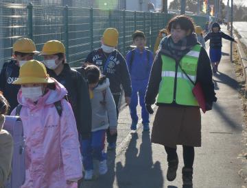 下校する子どもたちを見守るパトロール隊長の箕輪広美さん(右)=鉾田市上冨田