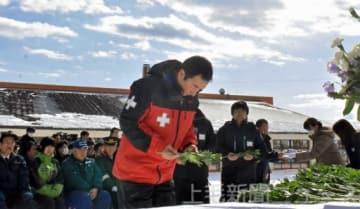 献花台に花を供え、伊沢陸曹長の冥福を祈る関係者