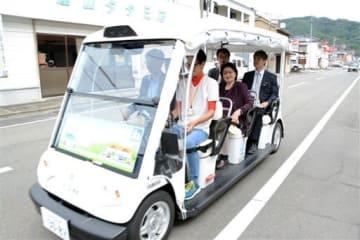 前回の短期実験で、住民らを乗せて道路を走る自動運転車。ドライバー(右手前)がハンドルから手を離した状態で走行した=2017年10月1日、芦北町