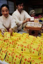 開運を願いながら、豆を袋に詰める巫女たち=湊川神社