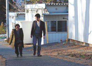 仮設住宅の坂道を歩く賢也さん(右)とテイさん。3月の閉鎖に伴い、別の仮設に引っ越す予定だ=岩手県山田町船越