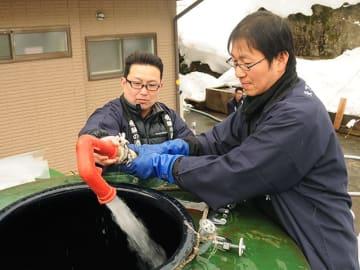 雪中酒の仕込みに向けて天生の湧き水をポンプでくみ上げる蔵人ら=飛騨市河合町元田