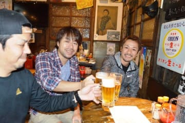 オリオンビールで乾杯する渡久地秀耶さん(右)ら=23日夜、那覇市安里の栄町ボトルネック
