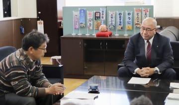 小笠原人志さん(左)と面会する岩手県大槌町の平野公三町長=24日午前、大槌町役場