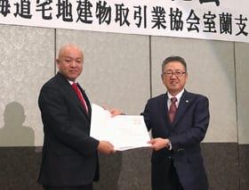 税制改正・住宅政策に関する提言書を渡す片岡支部長(右)と堀井議員
