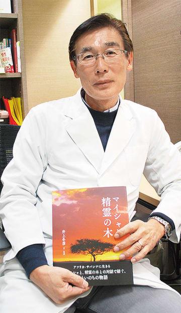 最新の写真絵本「マイシャと精霊の木」を手にする井上氏