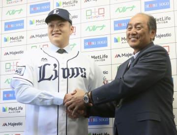 入団会見で、渡辺GM(右)と握手をする西武の廖任磊=24日、埼玉県所沢市の球団事務所