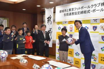 都城市との包括連携協定調印後、市内の小学校にボールを寄贈したFC東京・大金直樹社長(右端)