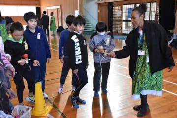 けん玉など伝統的な遊びを「世界青年の船」の外国人参加者に紹介し、交流を深めた田野小児童