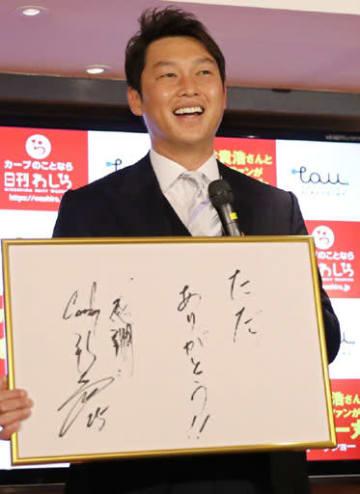 直筆のサインを手に笑顔を見せる新井さん(撮影・浜岡学)