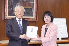 高橋知事に見舞金の目録を手渡す槙島専務(左)