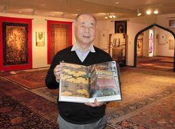 自身の「集大成」という本を手にする大熊克己さん=シルクロード絨毯ミュージアム