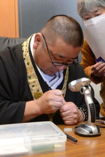米粒に念仏を書く小林住職(左)