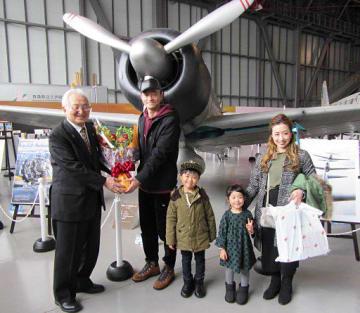 記念写真に納まる大柳館長(左端)と田原さん一家