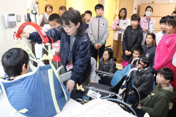在宅訓練室で介護器具の使い方などを学ぶ児童たち=大村市本町