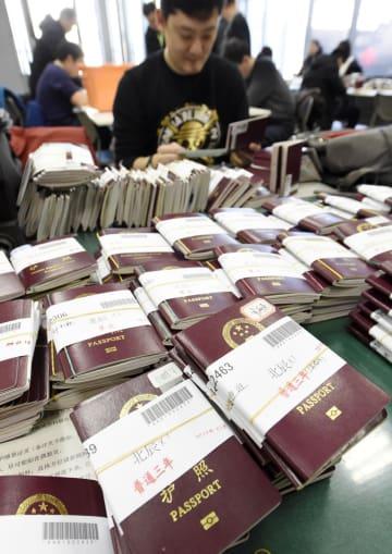 顧客から預かった大量のパスポートを前に、ビザ申請の作業をする旅行代理店の担当者=25日、北京の日本大使館(共同)