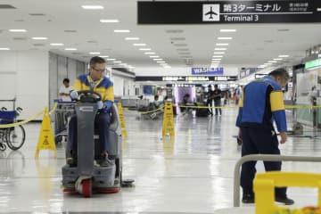 成田空港で清掃業務をする外国人従業員(左)=2018年