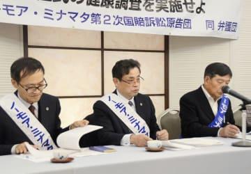 記者会見する、水俣病に関する国家賠償請求訴訟の熊本訴訟の園田昭人弁護団長(中央)ら=25日午後、熊本市
