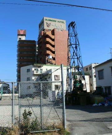 アマネクのリゾートホテル進出予定地(手前の空き地)と同社が買収したことが分かったホテル松美(奥の茶色の建物)=別府市駅前本町