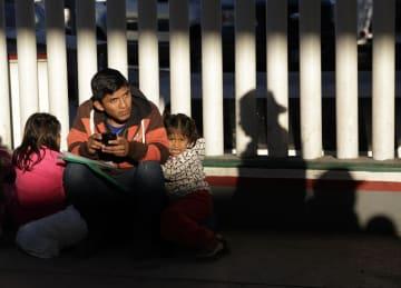 25日、米国と国境を接するメキシコ北西部ティフアナで、米国への難民申請手続きを待つ移民(AP=共同)