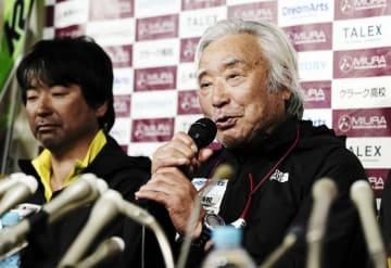 帰国報告会で話をする三浦雄一郎さん。左は次男豪太さん=26日午後、東京都渋谷区