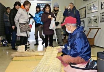 伝統文化のわら細工作りを見学するリゾート列車「雪月花」の乗客ら=26日、妙高市の新井駅