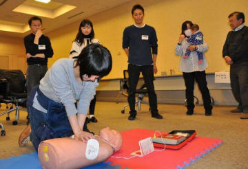 高橋さん(右から3人目)のアドバイスで心臓マッサージを体験する参加者ら=横浜市中区新港2丁目のJICA横浜